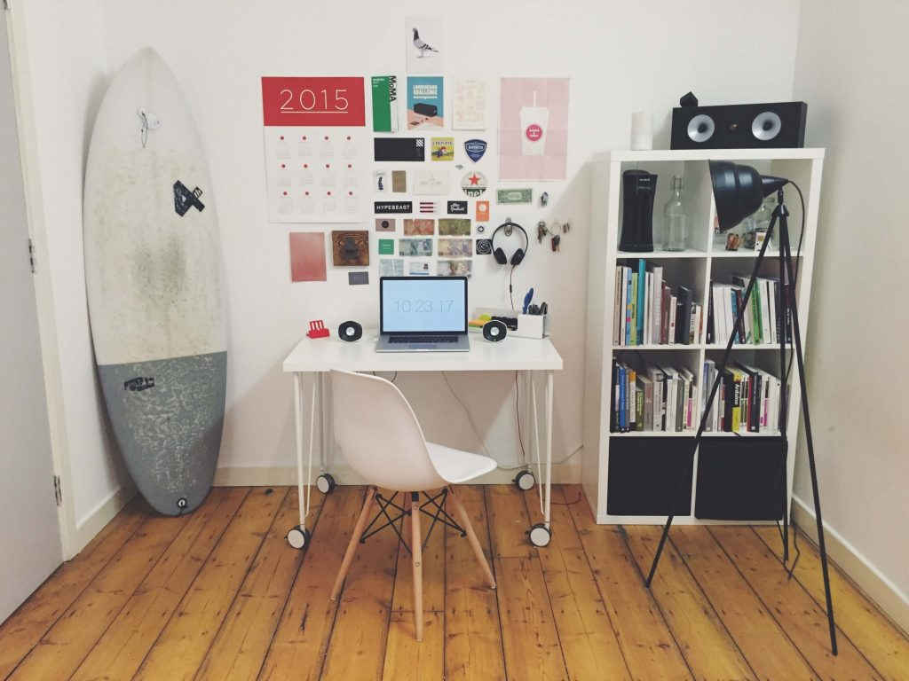 A room with a surfboard, desk and book case.